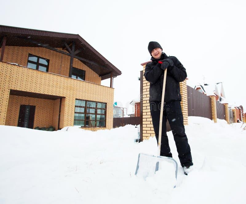 L'uomo pulisce la pala della neve vicino alla casa fotografie stock