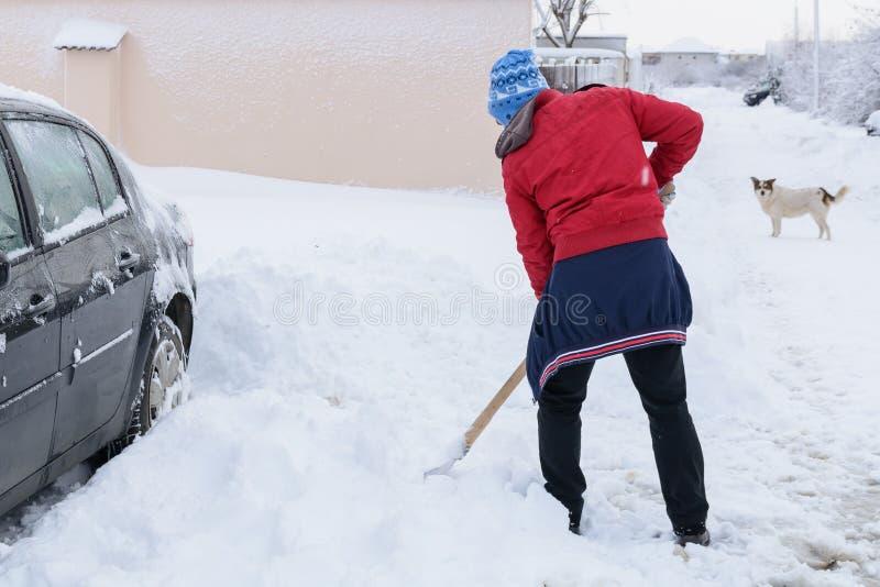 L'uomo pulisce la strada dopo una grande bufera di neve Neve di scavatura dell'uomo con lo sho fotografie stock