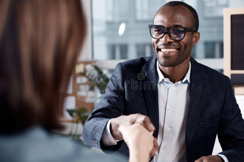 L'uomo qualificato ottimista sta intervistando signora immagini stock libere da diritti