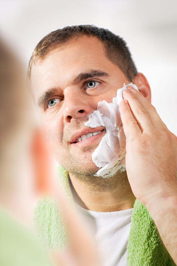 L'uomo rade il suo fronte immagine stock