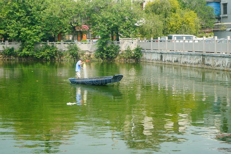 L'uomo reticolato in una barca di legno nello stagno immagine stock
