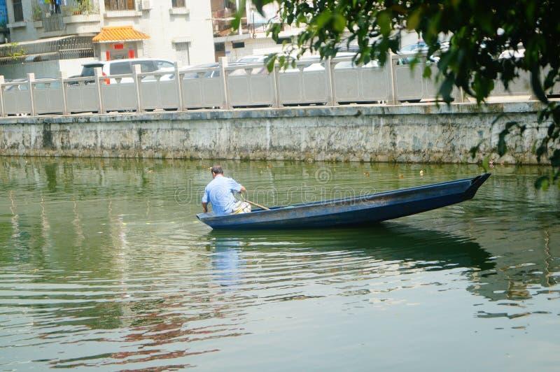 L'uomo reticolato in una barca di legno nello stagno fotografie stock libere da diritti
