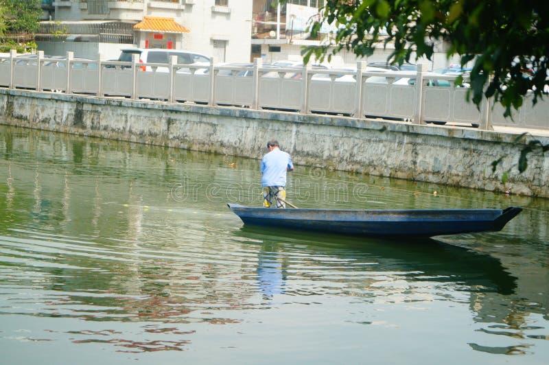L'uomo reticolato in una barca di legno nello stagno immagine stock libera da diritti