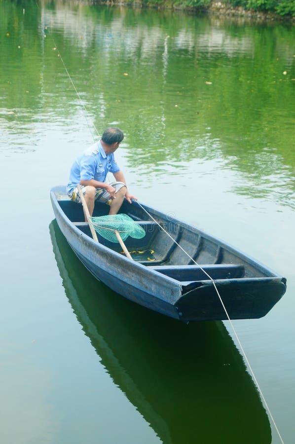 L'uomo reticolato in una barca di legno nello stagno immagini stock libere da diritti
