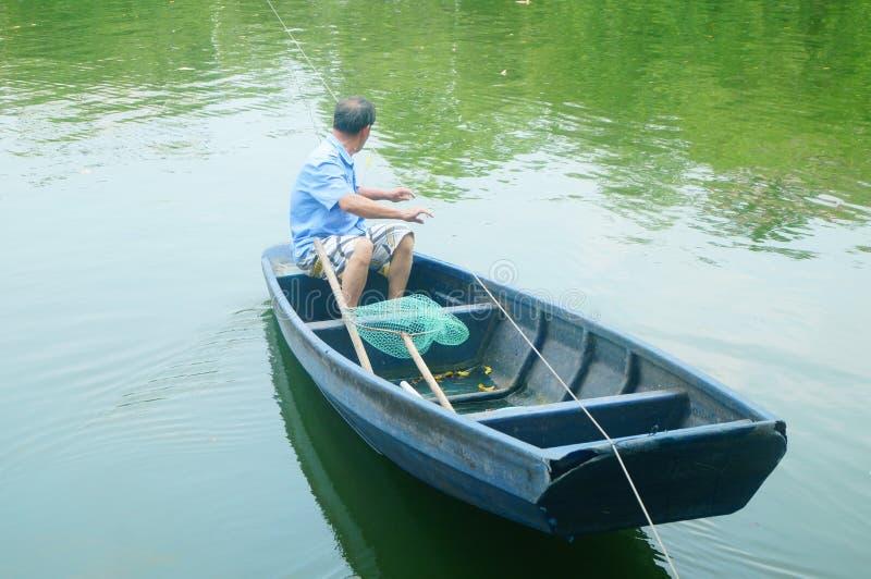L'uomo reticolato in una barca di legno nello stagno fotografia stock