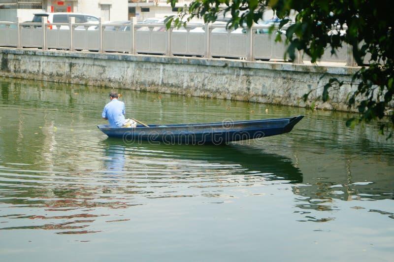 L'uomo reticolato in una barca di legno nello stagno fotografia stock libera da diritti
