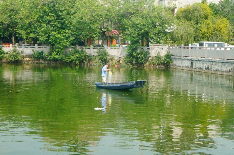 L'uomo reticolato in una barca di legno nello stagno fotografie stock