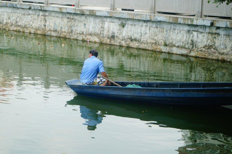 L'uomo reticolato in una barca di legno nello stagno immagini stock