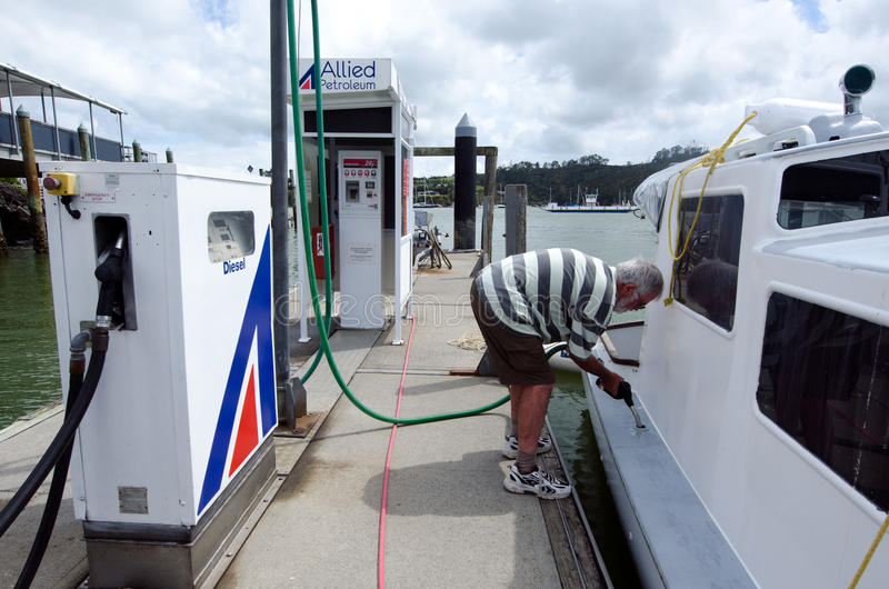 L'uomo rifornisce la sua barca di combustibile fotografia stock libera da diritti