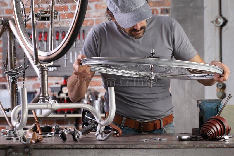 L'uomo ripara la bicicletta vintage in officina in garage sul banco di lavoro con attrezzi, concetto diy immagini stock