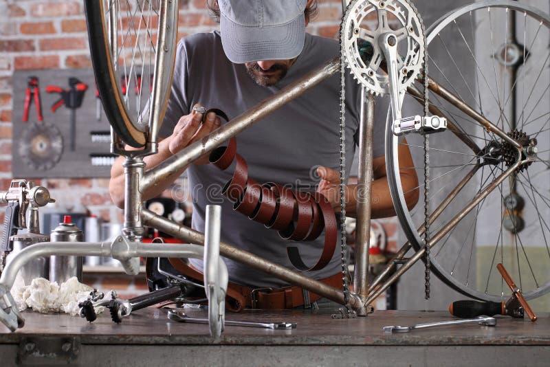 L'uomo ripara la bicicletta vintage in officina in garage sul banco di lavoro con attrezzi, concetto diy immagine stock