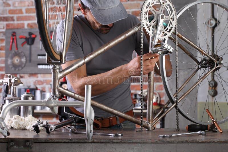 L'uomo ripara la bicicletta vintage in officina in garage sul banco di lavoro con attrezzi, concetto diy immagini stock libere da diritti