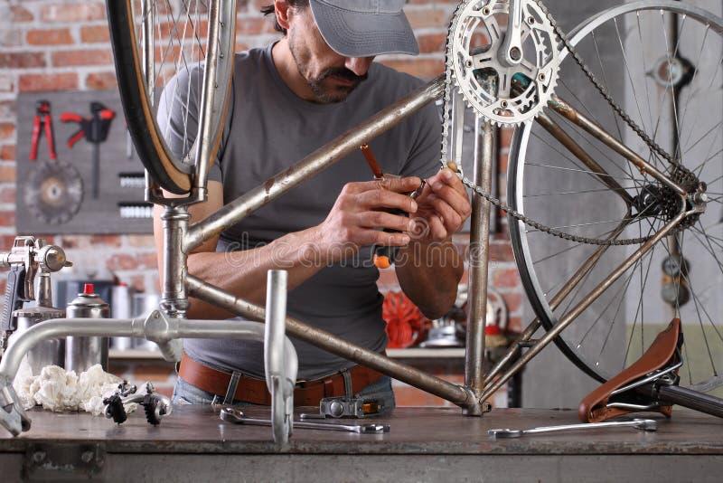 L'uomo ripara la bicicletta vintage in officina in garage sul banco di lavoro con attrezzi, concetto diy fotografia stock libera da diritti