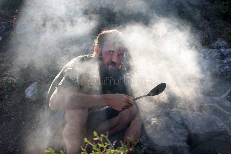 L'uomo a riposo con un grande cucchiaio al fuoco fotografie stock
