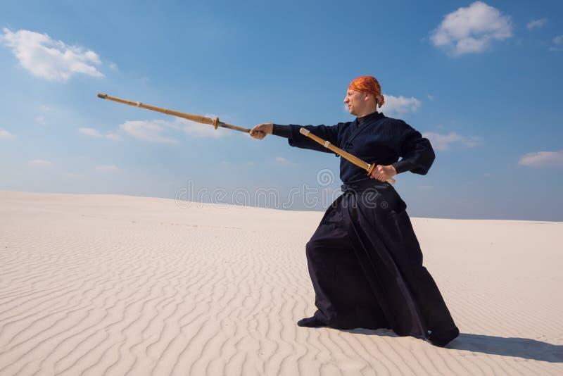 L'uomo risoluto con una spada di addestramento sta praticando le arti marziali immagine stock libera da diritti