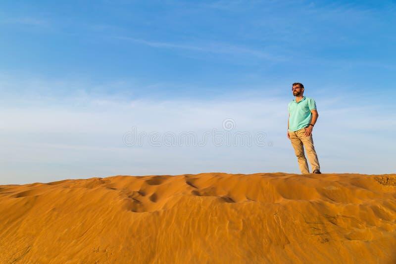 L'uomo riuscito con una barba in una maglietta del blu costa alla cima barkhan della duna nel deserto ad un backgr immagini stock libere da diritti