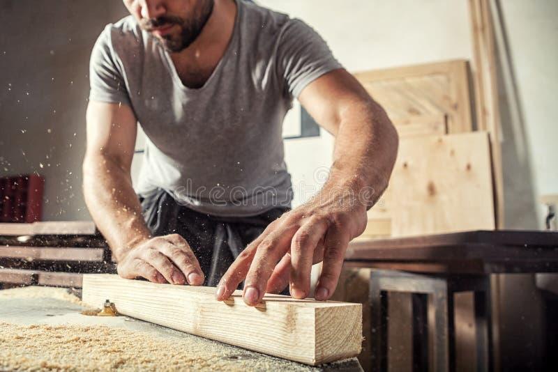 L'uomo ruba un di legno con una fresatrice fotografia stock