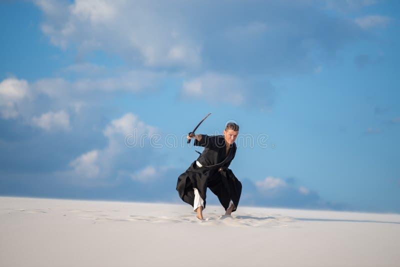 L'uomo salta con una spada giapponese, katana fotografia stock