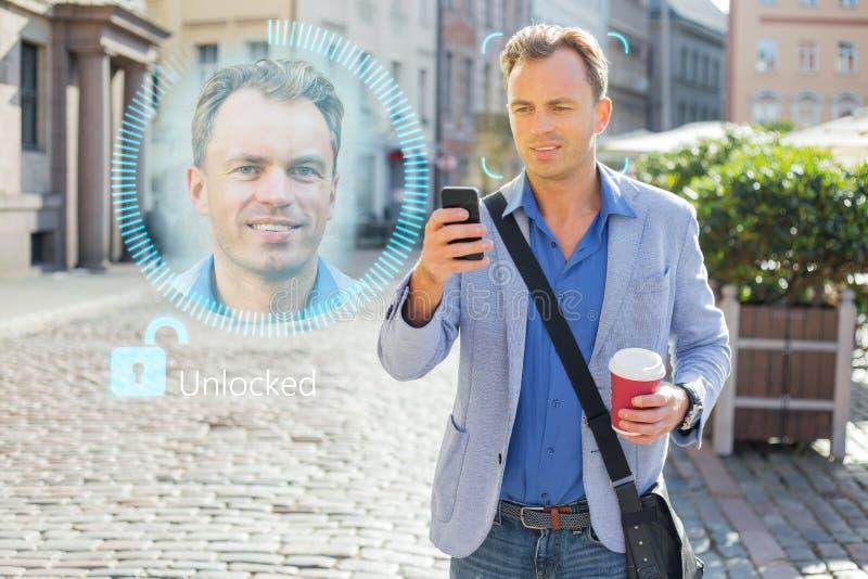 L'uomo sblocca il suo telefono cellulare con la tecnologia facciale dell'autenticazione e del riconoscimento immagini stock