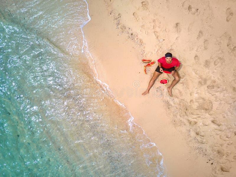 L'uomo scalzo sta mangiando l'anguria sulla spiaggia di sabbia fotografia stock