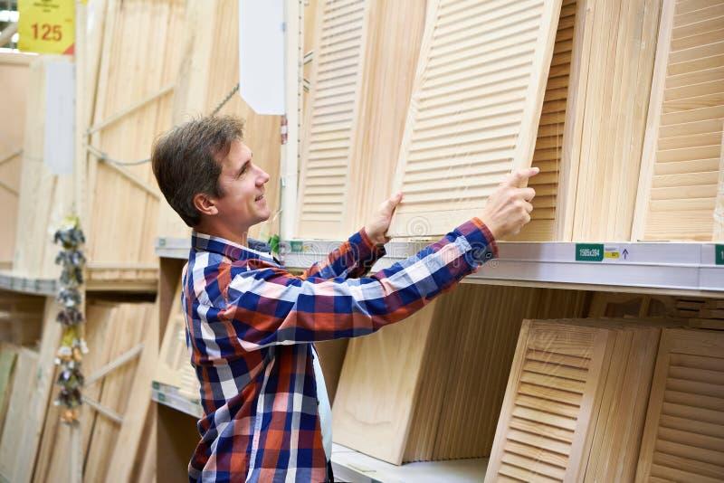 L'uomo sceglie le facciate di legno per mobilia in deposito fotografie stock libere da diritti