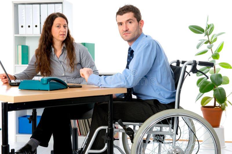 L'uomo in sedia a rotelle ed nella sua è collega femminile che lavora nel jo immagine stock libera da diritti