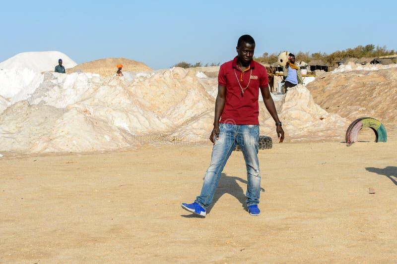 L'uomo senegalese non identificato in camicia e jeans rossi solleva la sua h fotografia stock libera da diritti