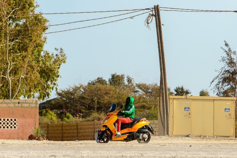 L'uomo senegalese non identificato guida un motociclo sul coa salato immagini stock libere da diritti