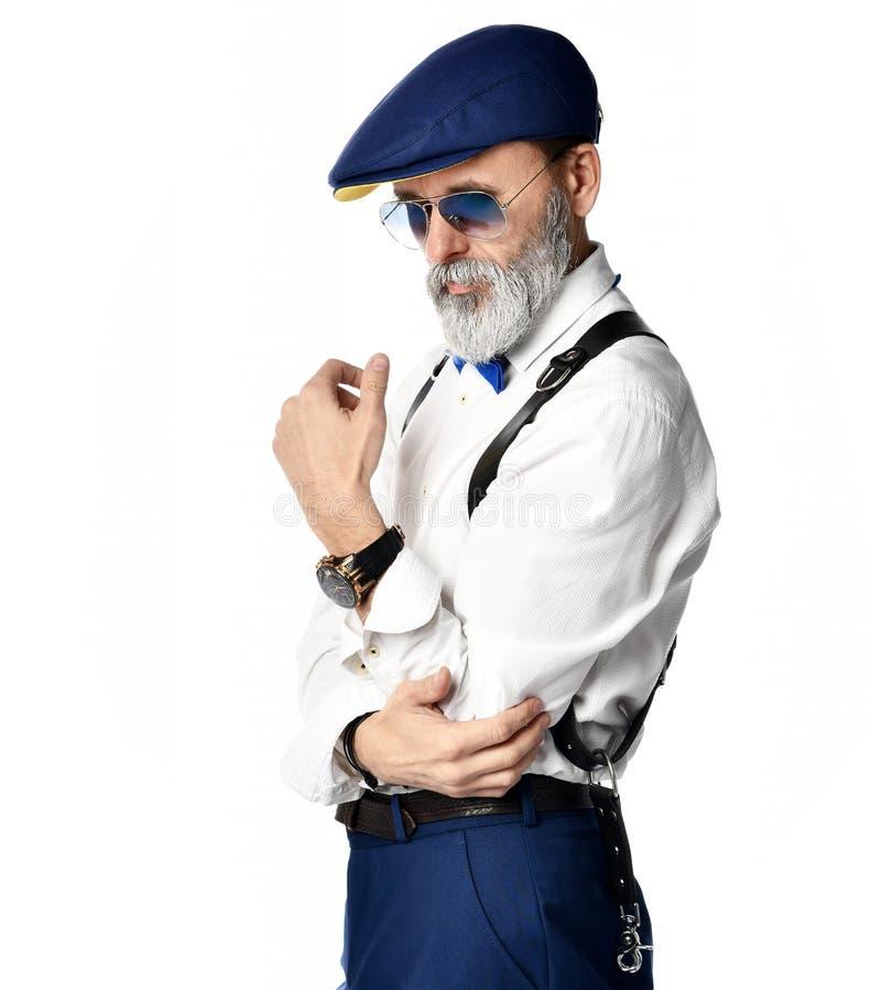 L'uomo senior brutale anziano del milionario in occhiali da sole bianchi dell'aviatore e della camicia pensa qualcosa sopra gli u fotografia stock