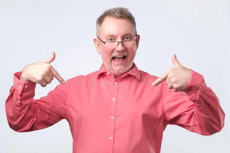 L'uomo senior in camicia e vetri rossi è fiero immagini stock libere da diritti