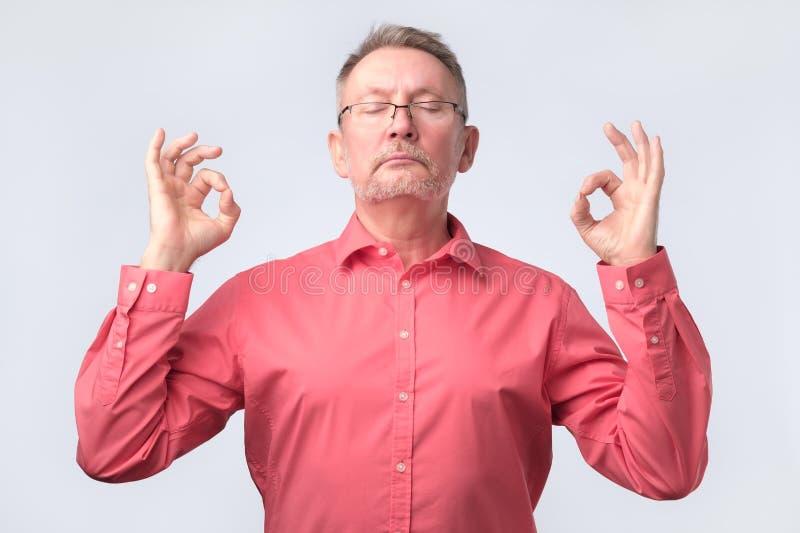 L'uomo senior in camicia rossa medita, prova a rilassarsi immagini stock