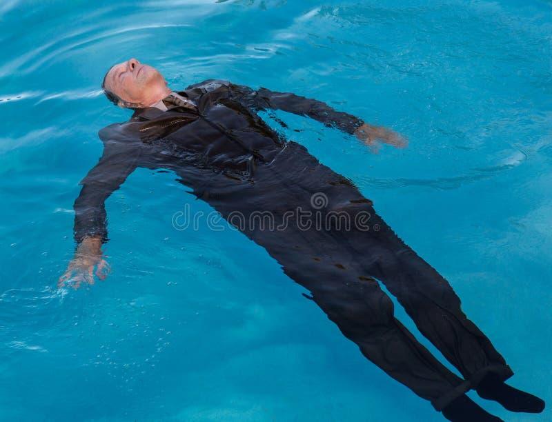 L'uomo senior che galleggia sopra appoggia in acqua fotografia stock