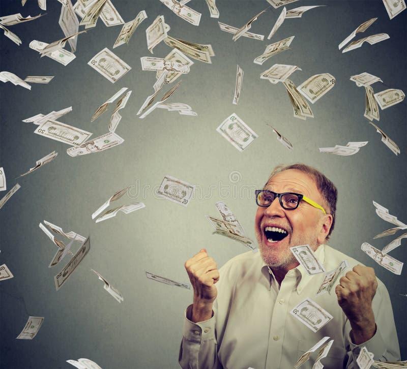 L'uomo senior che pompa i pugni estatici celebra il successo che grida sotto la pioggia dei soldi fotografie stock