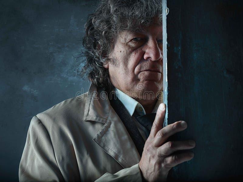 L'uomo senior come l'agente investigativo o capo della mafia sul fondo grigio dello studio immagini stock libere da diritti