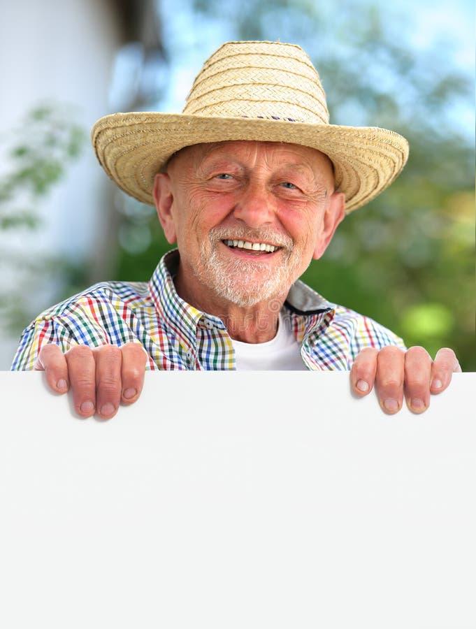 L'uomo senior con un cappello di paglia tiene un bordo in bianco fotografie stock