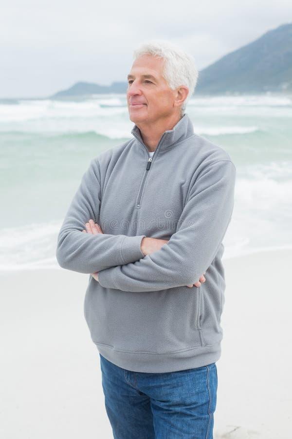 L'uomo senior contemplativo con le mani ha piegato alla spiaggia fotografie stock