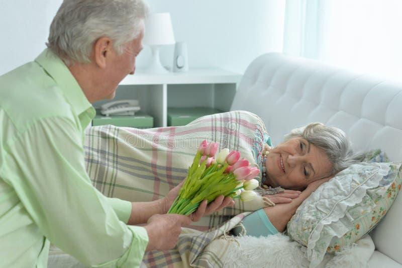 L'uomo senior dà i fiori ad una donna fotografie stock
