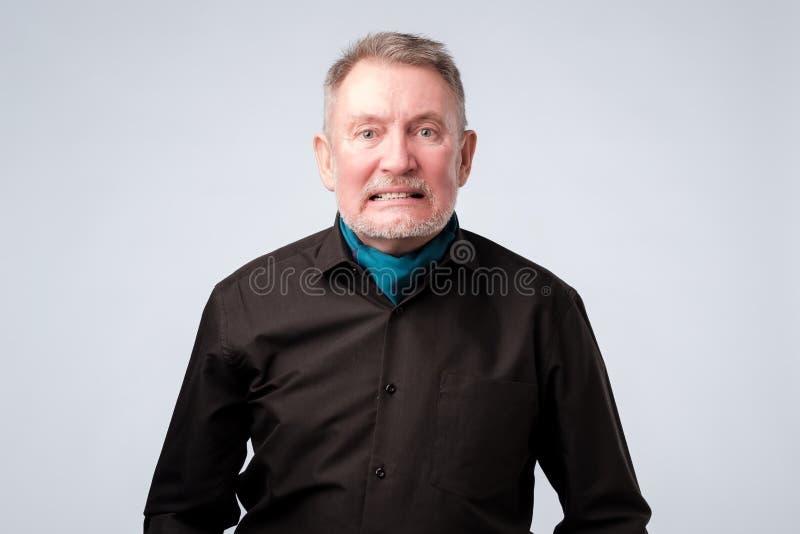 L'uomo senior ha irritato l'espressione, serra i denti, essendo malcontento, discute immagini stock