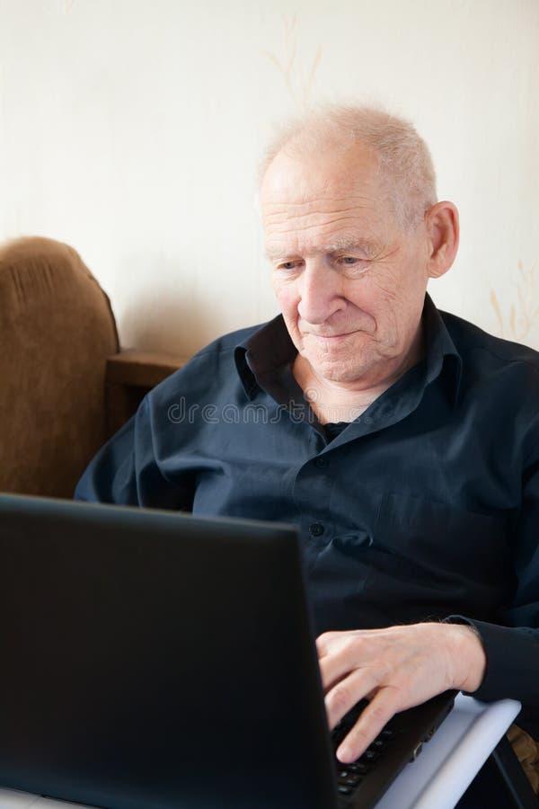 L'uomo senior nel nero sta lavorando ad un computer portatile fotografie stock