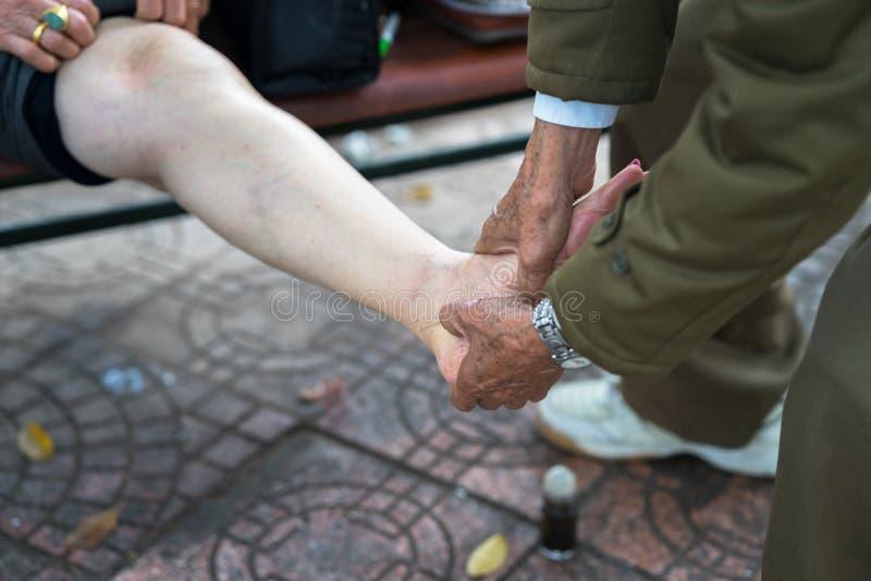 L'uomo senior passa fare il massaggio sulle gambe di dolore della donna anziana sulla via immagine stock