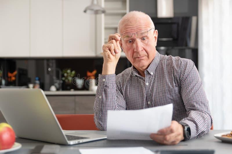 L'uomo senior si ? preoccupato per le fatture ed il risparmio immagine stock libera da diritti