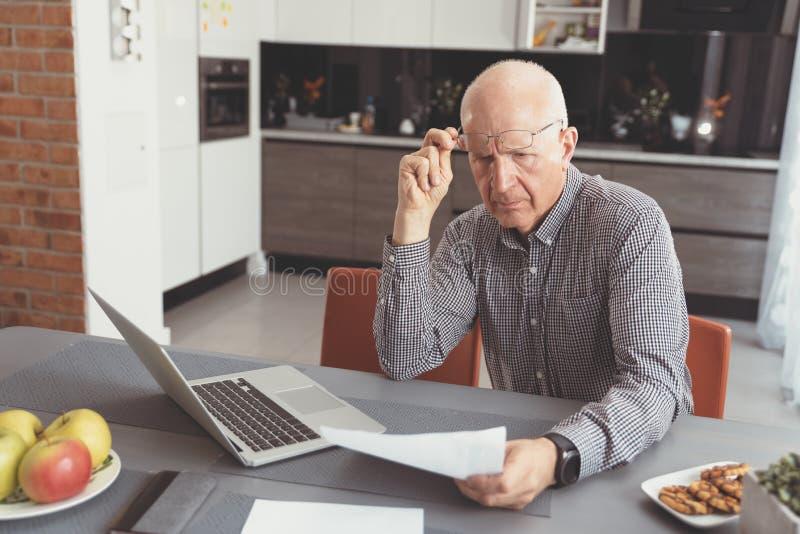 L'uomo senior si ? preoccupato per le fatture ed il risparmio immagini stock libere da diritti