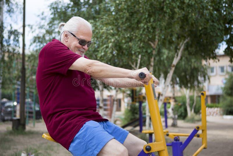 L'uomo senior si prepara su attrezzatura di sport su aria aperta fotografia stock