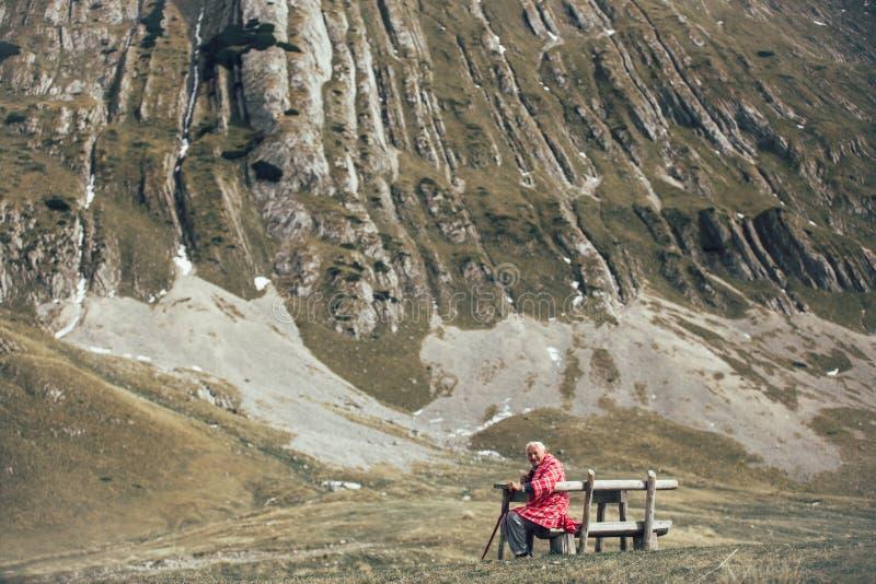 L'uomo senior sta sedendosi sul banco nella montagna fotografia stock libera da diritti