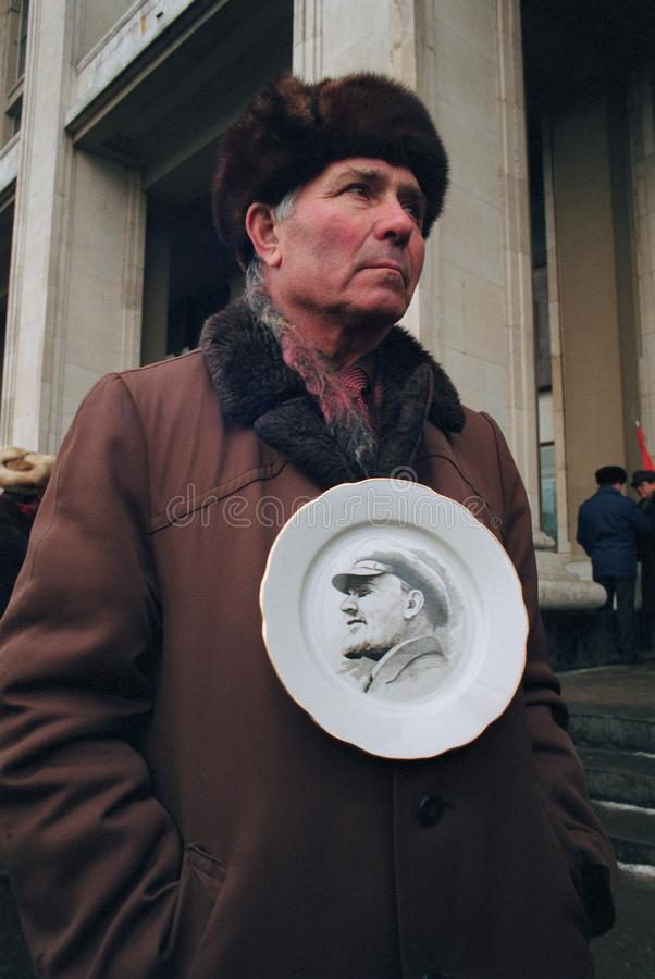 L'uomo senior tiene il piatto con il ritratto di Lenin immagine stock libera da diritti