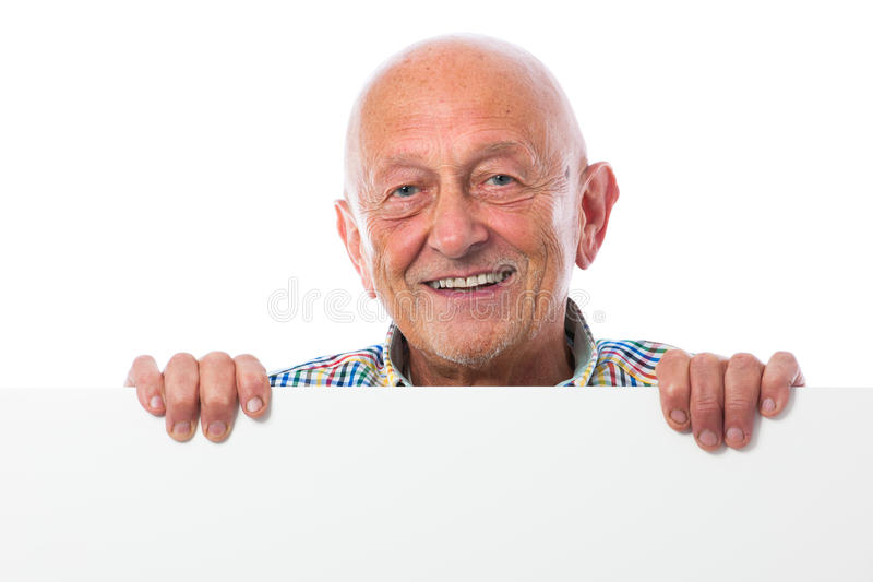 L'uomo senior tiene un bordo in bianco immagini stock