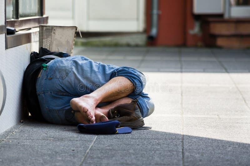 L'uomo senza tetto dorme sulla via, all'ombra della costruzione immagini stock libere da diritti