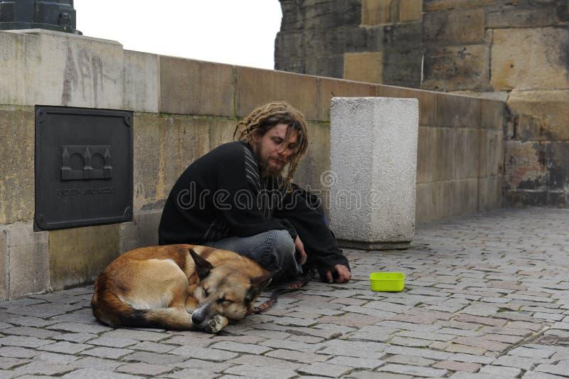 L'uomo senza tetto triste con un cane si siede e raccoglie le elemosine immagine stock