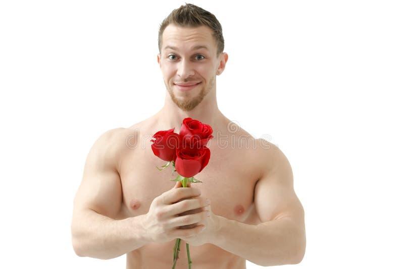 L'uomo sexy dà una rosa su un fondo bianco con una bella luce Isolato su priorità bassa bianca fotografia stock