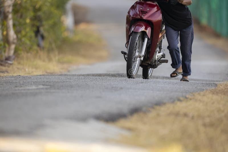 L'uomo sfortunato fa avanzare il motociclo morto fotografia stock libera da diritti
